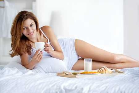 Natural smiling brunette holding a cup of tea in bright bedroom - beautiful young girl lying in bed with white porcelain cup photo
