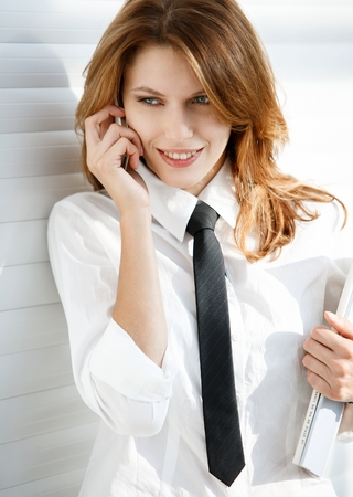 button down shirt: Business woman holding folder in her hand and talking on the phone - talkative woman in a white button down shirt with black tie