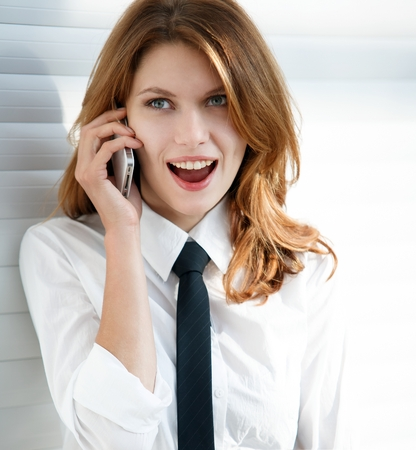 Beautiful young business woman talking on the phone - talkative woman in a white button down shirt with black tie