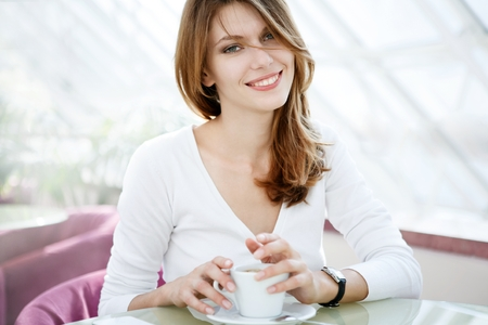 Holding a cup - photo of beautiful woman sitting in a coffee house Stock Photo