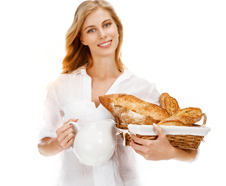 Traditional woman with bread and white carafe - portrait of young woman holding a wicker basket with bread and decanter with milk in her hands on white background photo