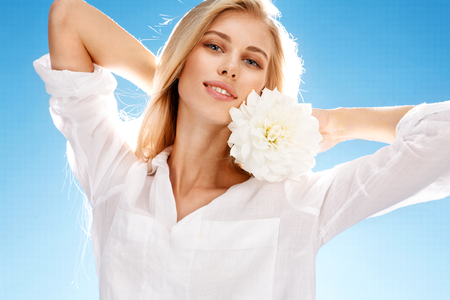 effloresce: Young beautiful healthy blond girl with peony - portrait of happy smiling girl with white flower in her hand on blue background Stock Photo