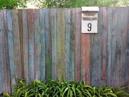 Village fence with address plate - outdoors photography of wooden fence photo