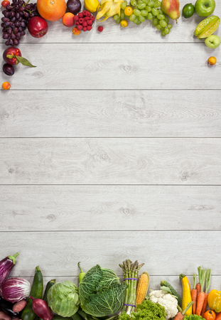 Healthy food background - studio photography of different fruits and vegetables on wooden table Standard-Bild