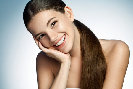 Portrait of a beautiful young Latina girl toothy smiling - photograph of a cute brunette smiling girl on studio background photo
