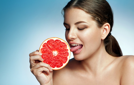 Pretty girl licking grapefruit - photoset of attractive girl holding a cut piece of Sicilian orange on blue background
