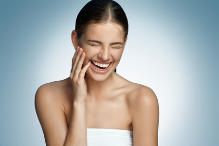 LOL (hardop lachen, hardop lachen, veel gelach) - portret van een jonge mooie brunette meisje lachend op een blauwe achtergrond
