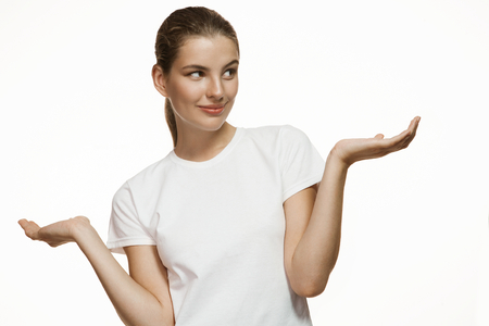 gesticulating: Nice girl with palms up - Gorgeous girl in plain white T-shirt. Mixed race Latina Caucasian young woman gesticulating - isolated on white background.