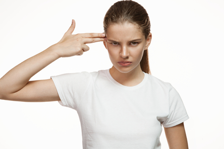 Depressed girl suicide gesture - Gorgeous girl in plain white T-shirt. Mixed race Latina Caucasian young woman gesticulating - isolated on white background.