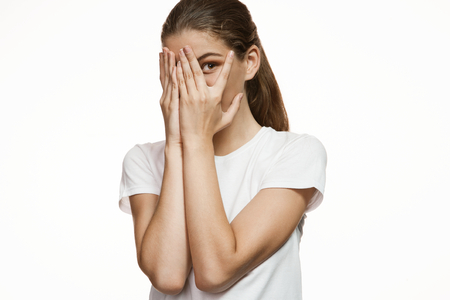 keek: Girl covering face with hands, hiding face with hands - Gorgeous girl in plain white T-shirt. Mixed race Latina Caucasian young woman gesticulating - isolated on white background.
