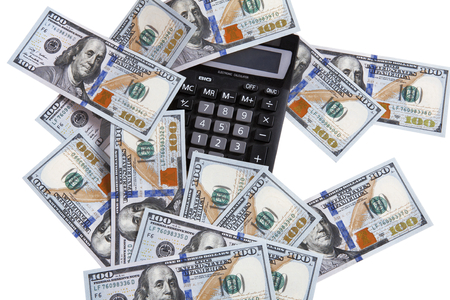 Pocket digital calculator and dollars - studio photography of USD and a small electronic device with a keyboard and a visual display photo