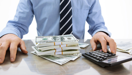 Hard money lender - close-up photo of successful boss working with calculator in the office