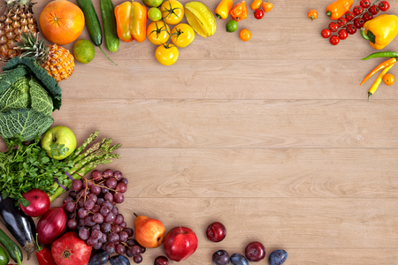 fruits background: Healthy eating background - studio photography of different fruits and vegetables on wooden table