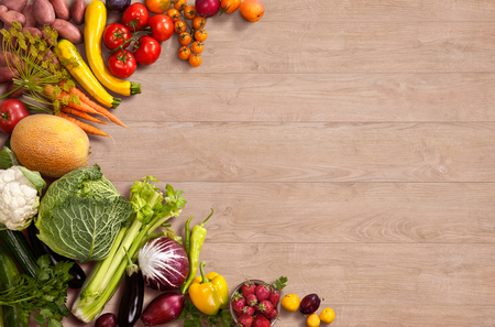 Healthy food background - studio photo of different fruits and vegetables on wooden table