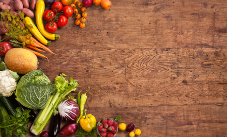 food production: Healthy food background - studio photo of different fruits and vegetables on old wooden table