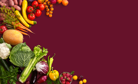 Superfood background - studio photo of different fruits and vegetables on red backdrop Stock Photo