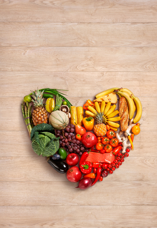 food photography: Heart symbol - food photography of heart made from different fruits and vegetables on wooden table Stock Photo