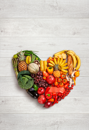 Heart symbol - food photography of heart made from different fruits and vegetables on wooden table Stockfoto