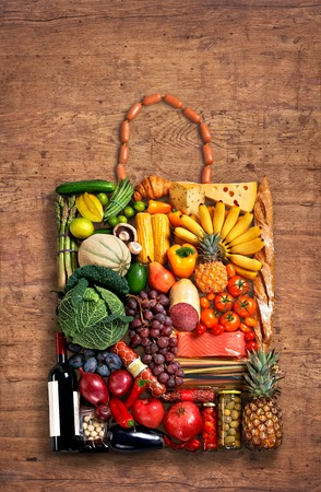 food photo of handbag made from different fruits and vegetables on old wooden table photo