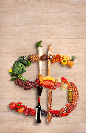 photography of dollar sign made of fruits, vegetables and other products on wooden table photo