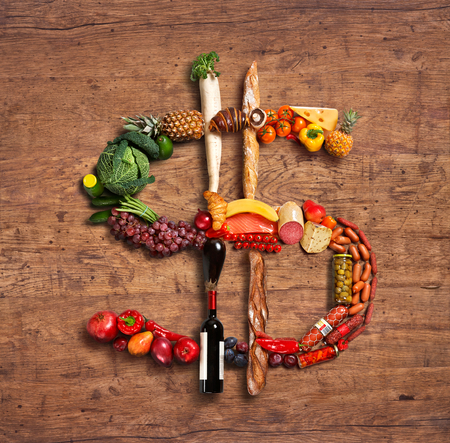 photography of dollar sign made of fruits, vegetables and other products on old wooden table photo