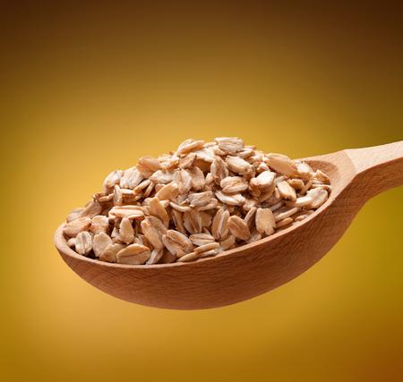 avena en hojuelas: Copos de avena en una cuchara de madera - cereales en cucharas de madera aislada sobre fondo de oro Foto de archivo