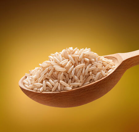 unpolished: Unpolished rice in a wooden spoon - cereal on wooden spoons isolated on golden background