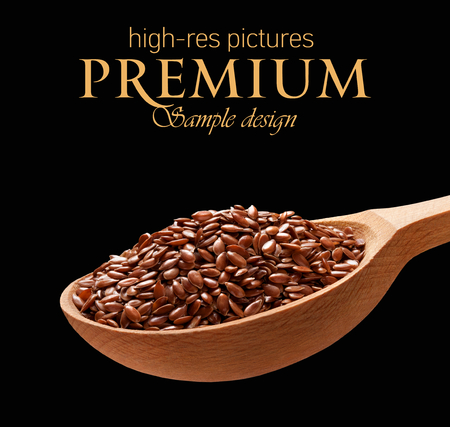 organic flax seed: Linseed in a wooden spoon - cereal on wooden spoons isolated on black background with place for your text Stock Photo
