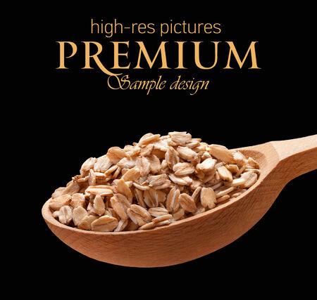 avena en hojuelas: Copos de avena en una cuchara de madera - cereales en cucharas de madera aisladas sobre fondo negro con lugar para el texto Foto de archivo
