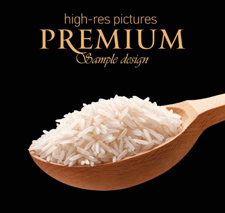 Basmati rijst in een houten lepel - graan op houten lepels geïsoleerd op zwarte achtergrond met plaats voor uw tekst Stockfoto