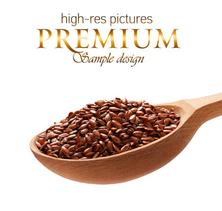 organic flax seed: Linseed in a wooden spoon - cereal on wooden spoons isolated on white background with place for your text