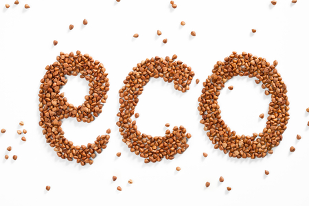 groats: Word ECO composed of premium buckwheat groats on white background Stock Photo