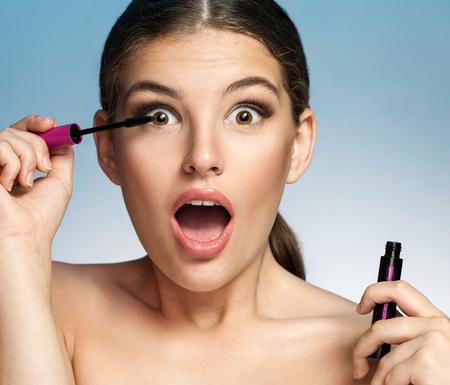 femme bouche ouverte: Femme surprise avec Mascara - la photographie de fille brune avec sa bouche ouverte contre fond bleu Banque d'images