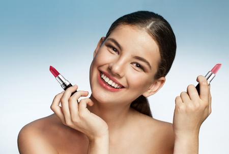 Beautiful young woman with lipstick - photography of brunette girl with red colored pomade on blue background