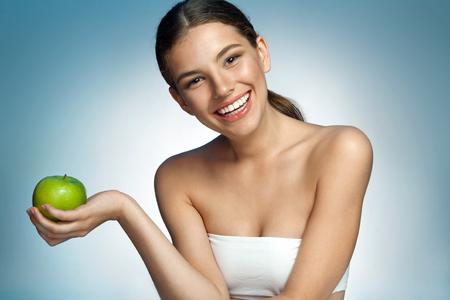 ハッピーと健康、自然有機ローフード新鮮なコンセプト - 魅力的な微笑の女の子彼女の手で緑のリンゴをかざす青い背景の肖像画