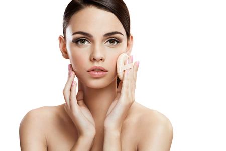 パウダーパフ、肌ケアの概念と彼女の顔に頬紅を適用する若い女性