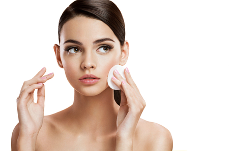 Beautiful brunette woman removing makeup from her face, skin care concept Stock Photo