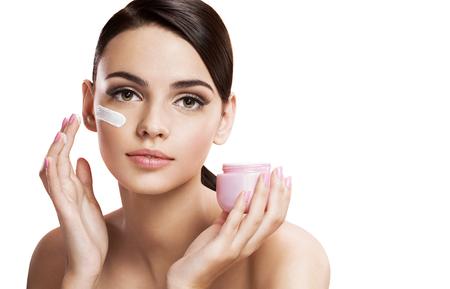 mujer maquillandose: Hermosa mujer joven aplicar crema hidratante, el concepto de cuidado de la piel Foto de archivo