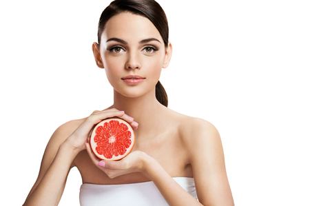 Young woman with grapefruit cut in half, healthy life concept photo