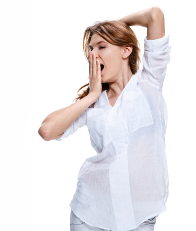 Tired woman yawns and covers her mouth with her hand Zdjęcie Seryjne