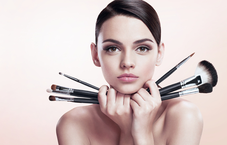 young teen girl nude: Young beautiful teen girl with makeup brushes near her face, skin care concept