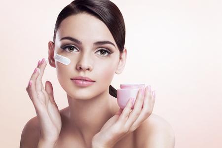 Beautiful young lady applying moisturizing creme 스톡 콘텐츠