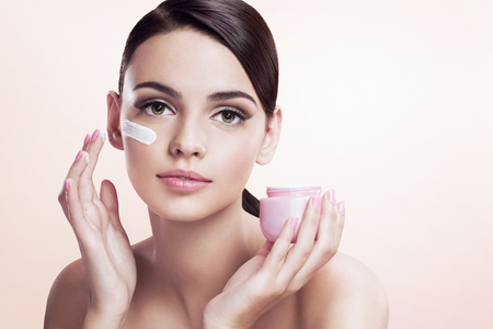 Beautiful young lady applying moisturizing creme Stock Photo