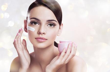美しい若い女性は保湿クリームは、肌のケアの概念を適用します。