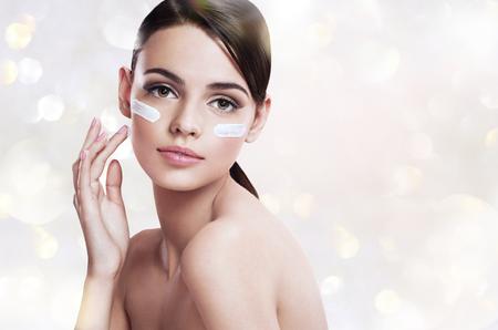 caras de emociones: Mujer del cuidado de piel que pone la crema para la cara