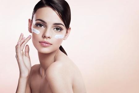 mujer maquillandose: Dama cuidado de piel que pone la crema de cara Foto de archivo