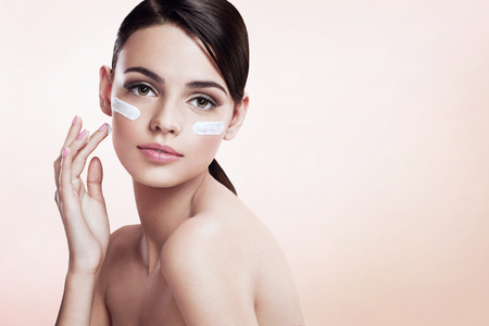 face: Skin care lady putting face cream Stock Photo