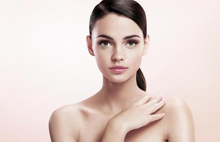 プロのメイクが、肌ケアのコンセプト - ベージュ色の背景に魅力的なブルネットの少女の写真植字のかなり若い女性