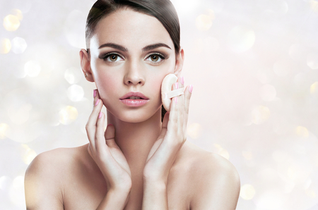 ほお紅パウダーパフ、肌のケアの概念と彼女の顔に適用する若い女性