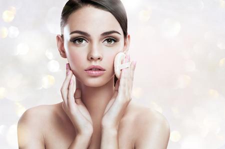 Joven aplicar colorete en la cara con el soplo de polvo, el concepto de cuidado de la piel Foto de archivo - 38022182